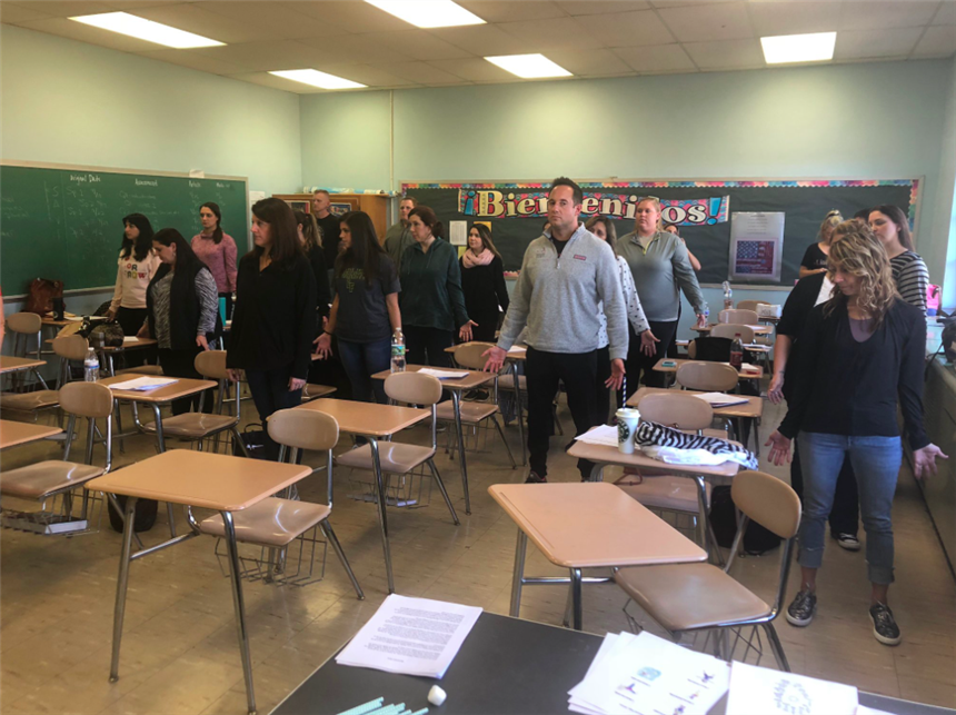 Teachers partake in Sun Salutation dance in classroom; photo credit: Ms. Rae Allex